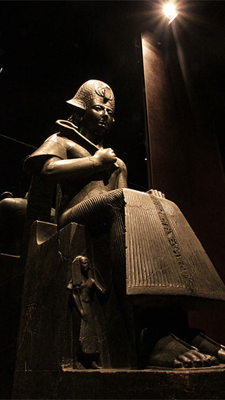 A statue sitting on throne at the Egyptian Museum lit by latest technology LEDs by Philips Lighting