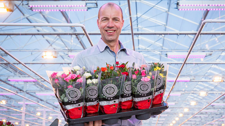 Leo van der Harg is posing with colorful flowers in his hands.