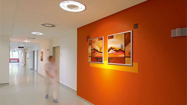 Nurse is walking in a lit corridor by Philips at the psychiatric clinic