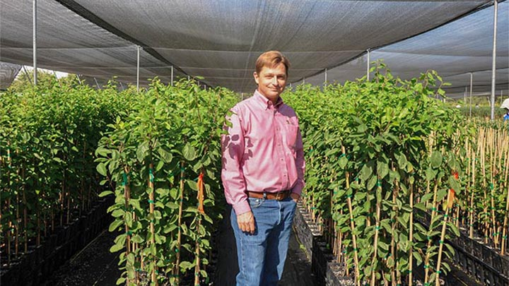 Cliff Beumel posing at Sierra Gold Nurseries lit up with energy-efficient plant grow lights by Philips