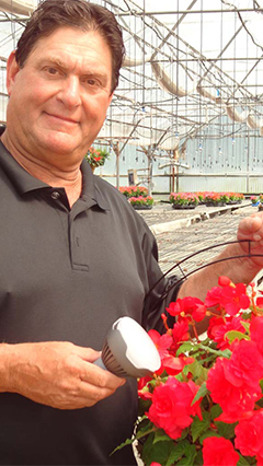 A man holds a plant at Valley View Greenhouses, as well as a Philips LED flowering light