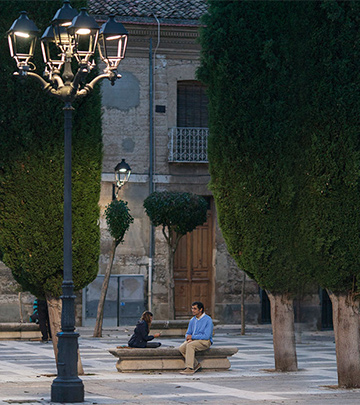 Man and child playing cards on street of Palencia lit by Philips lighting