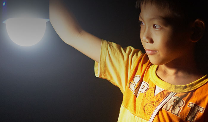 Boy looking into lightbulb