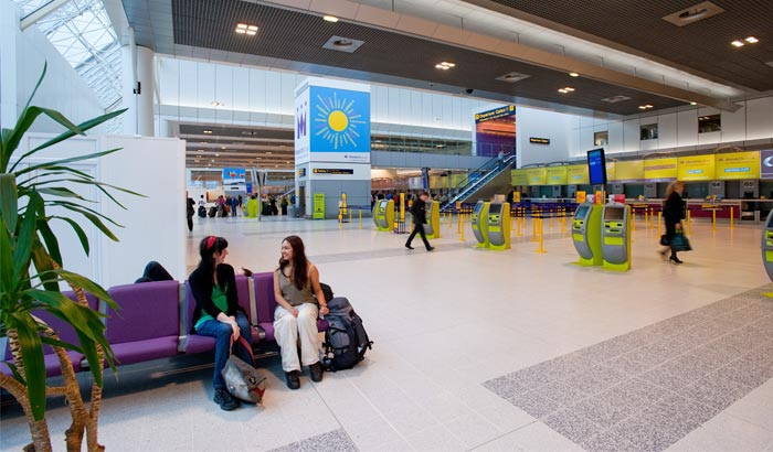 Two women converse in the Manchester Airport Terminal 2 under LED ceiling lighting