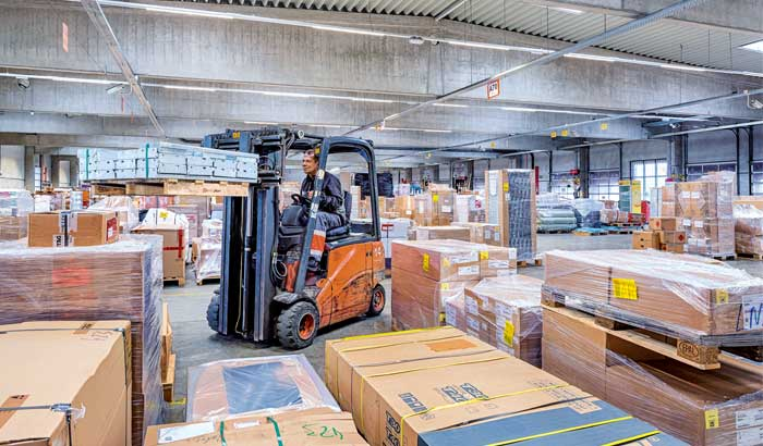A worker operates a forklift to move palettes in a warehouse